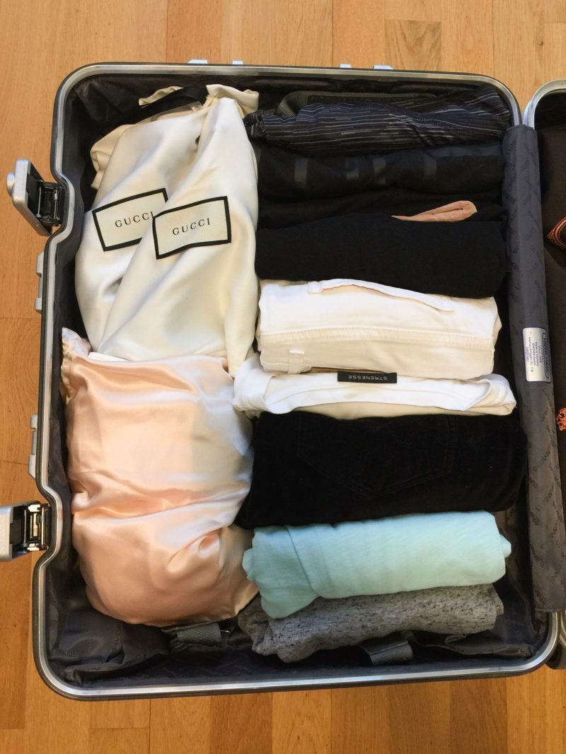 Packed suitcase: rolled clothes and shoes in shoe bags